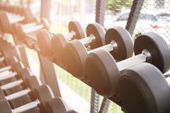 Fila de pesas de gimnasia en gimnasio Pesa de gimnasia negra fijada en el CEN de la aptitud del deporte Imagen de archivo libre de regalías