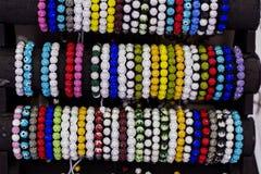 Fila de pulseras coloridas en mercado de la joyería Fotografía de archivo libre de regalías