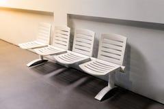 Fila de sillas blancas plásticas en el vestíbulo Fotografía de archivo libre de regalías