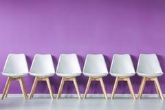 Fila de sillas contra la pared imagen de archivo