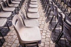 Fila de sillas envejecidas viejas en el día del concierto de la ceremonia en luz del día Foto de archivo