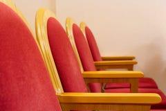Fila de sillas rojas en un primer vacío de la sala de conciertos imagenes de archivo