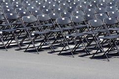 Fila de sillas vacías negras Imagenes de archivo