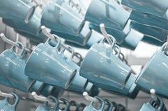 Fila de tazas azules en la exhibición Fotografía de archivo