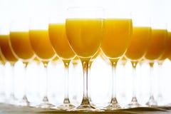 Fila de vidrios con el zumo de naranja fresco Fotos de archivo libres de regalías