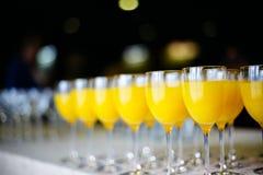 Fila de vidrios con el zumo de naranja fresco Foto de archivo libre de regalías