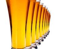 Fila de vidrios con la cerveza de cerveza dorada Imagen de archivo