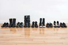 Fila de zapatos y de cargadores del programa inicial en un suelo de madera Imágenes de archivo libres de regalías