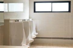 Fila degli orinali bianchi dell'interno per l'uomo nella toilette, lavabo di lusso moderno di progettazione immagini stock libere da diritti