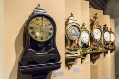 Fila degli orologi assortiti della mensola del camino del pendolo Immagini Stock