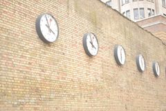 Fila degli orologi su un muro di mattoni fotografia stock libera da diritti
