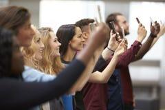Fila degli studenti all'università che prende le foto con gli smartphones Fotografia Stock Libera da Diritti