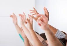 Fila degli studenti di college che sollevano le mani fotografia stock libera da diritti