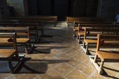 Fila dei banchi di legno dentro una chiesa Fotografie Stock