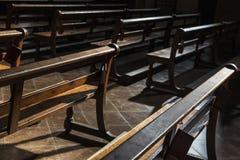 Fila dei banchi di legno dentro una chiesa Immagine Stock