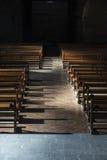 Fila dei banchi di legno dentro una chiesa Immagini Stock
