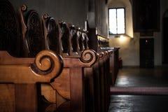 Fila dei banchi di legno dentro una chiesa in Spagna Fotografia Stock