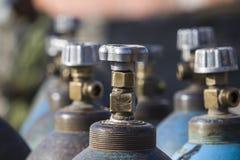Fila dei contenitori industriali liquefatti del gas dell'ossigeno con le valvole Chiuda su delle valvole fotografia stock