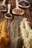 Fila dei cucchiai di legno con le spezie su fondo d'annata, prospettiva di diminuzione, primo piano, fuoco selettivo Immagini Stock