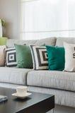 Fila dei cuscini sul sofà grigio moderno Fotografia Stock