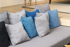 Fila dei cuscini sul sofà in salone fotografia stock