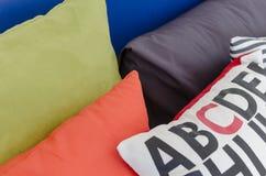 Fila dei cuscini variopinti sul letto Immagini Stock Libere da Diritti