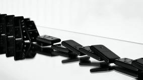 Fila dei domino che cadono più sullo specchio video d archivio