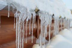 Fila dei ghiaccioli sul tetto della casa Immagini Stock