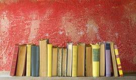 Fila dei libri d'annata su fondo rosso Immagine Stock