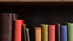 Fila dei libri d'annata variopinti su un vecchio scaffale per libri Fotografie Stock Libere da Diritti
