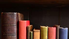 Fila dei libri d'annata variopinti su un vecchio scaffale per libri Immagine Stock