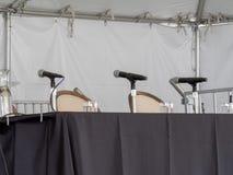 Fila dei microfoni che si siedono sulla tavola, in attesa gli altoparlanti fotografia stock libera da diritti
