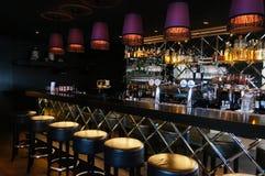 Fila dei panchetti e del contatore della barra in ristorante accogliente vuoto Fotografia Stock