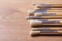 Fila dei pennelli sul fondo della tavola Immagine Stock