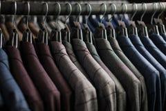 Fila dei rivestimenti del vestito degli uomini sui ganci Fotografia Stock Libera da Diritti