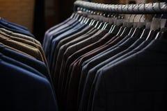 Fila dei rivestimenti del vestito degli uomini sui ganci Immagini Stock