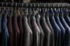 Fila dei rivestimenti del vestito degli uomini sui ganci Fotografia Stock