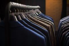 Fila dei rivestimenti del vestito degli uomini sui ganci Fotografie Stock