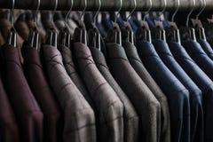 Fila dei rivestimenti del vestito degli uomini sui ganci Immagine Stock Libera da Diritti