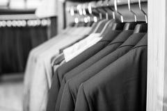 Fila dei rivestimenti sui ganci nel negozio di vestiti degli uomini Fotografia Stock
