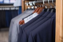 Fila dei rivestimenti sui ganci nel negozio di vestiti degli uomini Immagini Stock