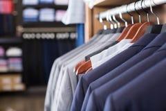 Fila dei rivestimenti sui ganci nel negozio di vestiti degli uomini Immagine Stock Libera da Diritti