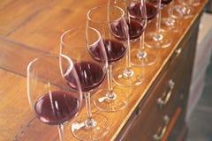 Fila dei vetri con vino rosso Fotografia Stock