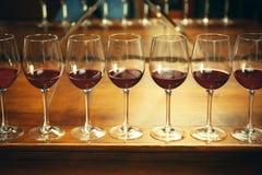 Fila dei vetri con vino rosso Fotografia Stock Libera da Diritti