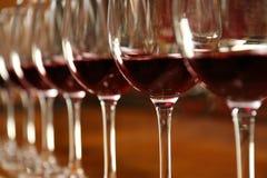 Fila dei vetri con vino rosso sul contatore della barra, Fotografie Stock Libere da Diritti
