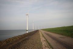 Fila del generatore eolico lungo la riva del IJsselmeer con il ponte di camminata a  Fotografia Stock Libera da Diritti
