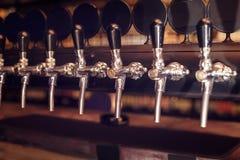 Fila del rubinetto della birra Rubinetti della birra nella barra immagini stock