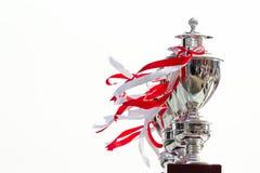 Fila del trofeo atada con la cinta blanca y roja en el fondo blanco Fotos de archivo libres de regalías
