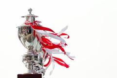 Fila del trofeo de la taza atada con la cinta blanca y roja en el backgr blanco Fotografía de archivo libre de regalías