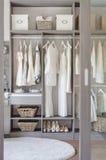 Fila del vestido blanco y negro con los zapatos en guardarropa imagenes de archivo
